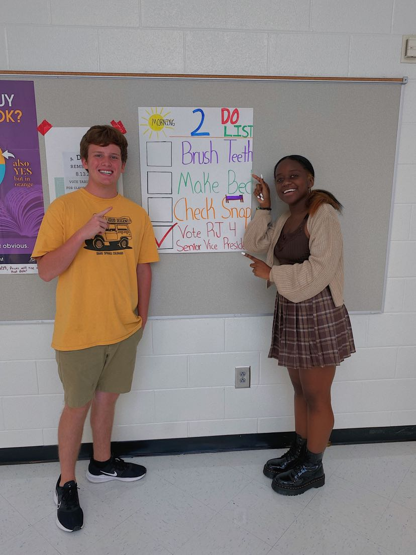 Kimberly and RJ standing next to their camping poster: Whats a good campaign without a little publicity?